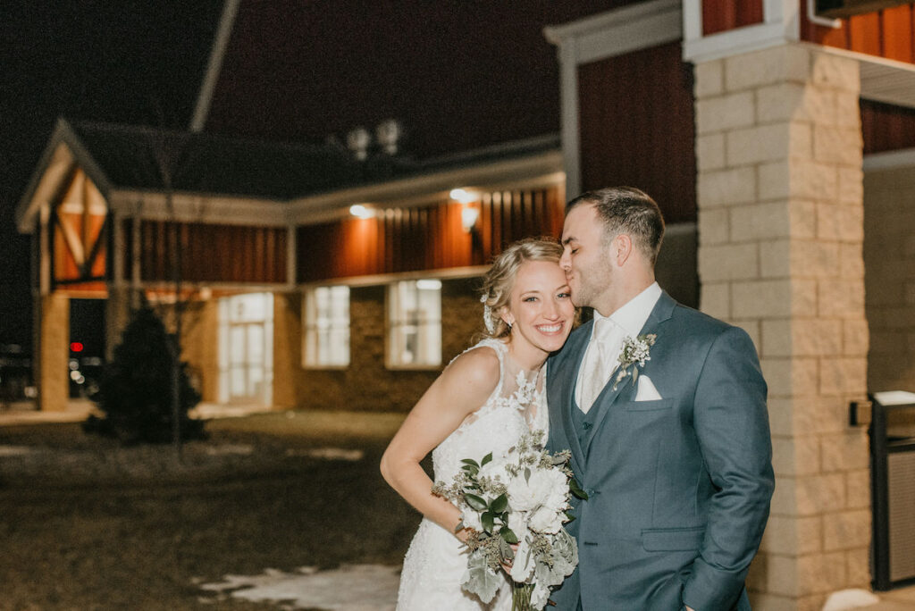 Bride and groom outside of barn building